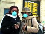 Dos mujeres con mascarillas sanitarias en la Estación Central de Milán (Italia).