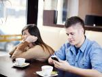 Una pareja toma algo en una cafetería: el mira el móvil y ella se aburre.