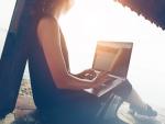 Persona trabajando con un ordenador en la playa