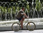 Un hombre pasea con su bicicleta por un parque de Madrid.